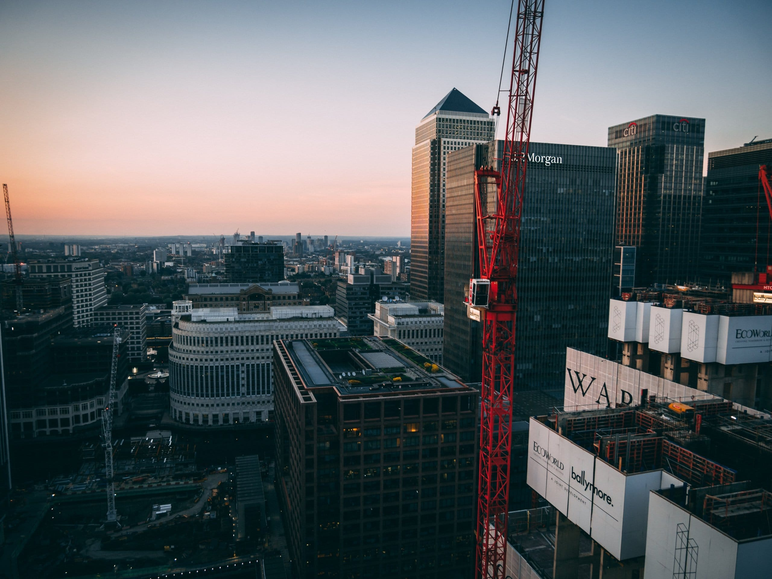 red tower crane between buildings
