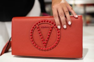 person holding red leather handbag